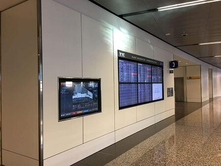 Examples of High-Traffic Spaces Where HPL Cladding Thrives - Airport Hallway with TVs