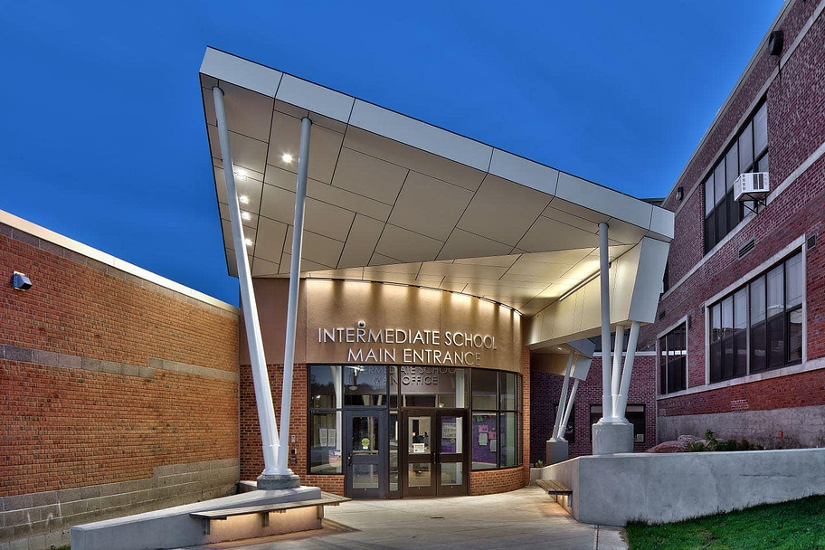 Front entryway of Sodus High School in New York lit up showcasing Fundermax's HPL panels.