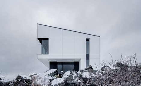 Shift house in Canada using white exterior phenolic panels and a concealed fastener.