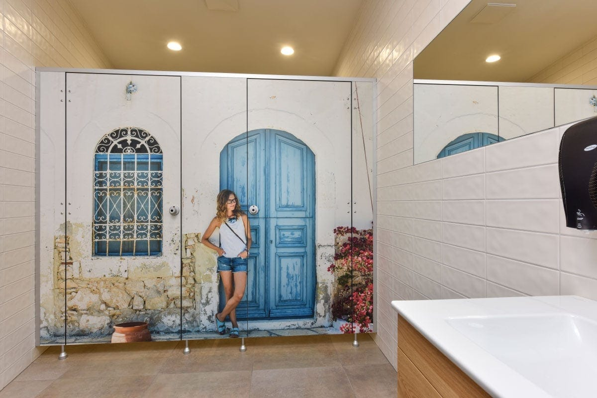 Custom HPL bathroom partition with woman leaning against a door