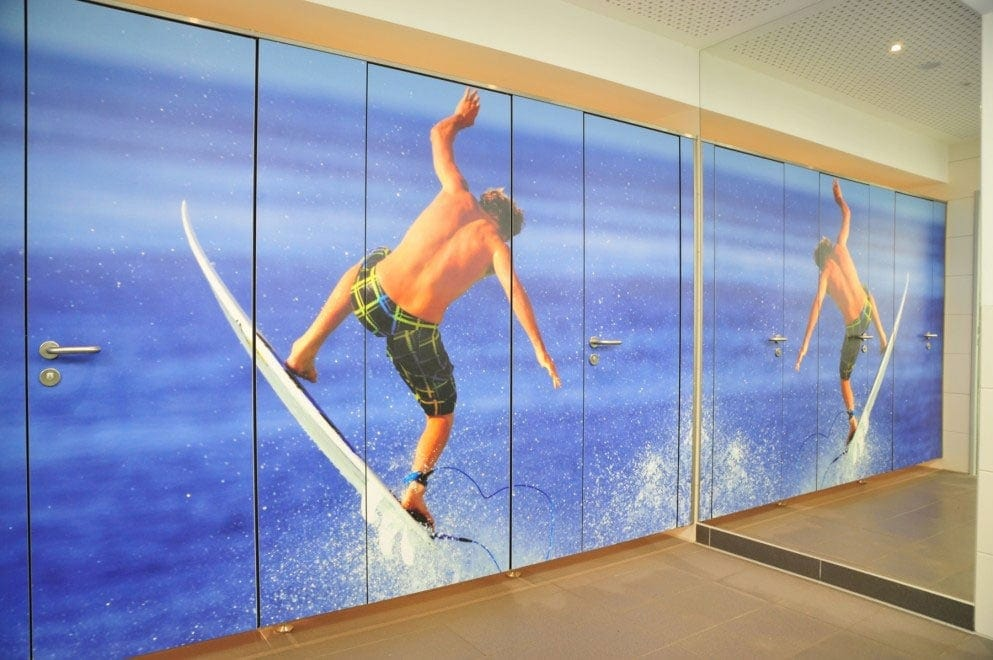 Fundermax Max Compact Interior phenolic panels customized via Individualdécor for image of surfer on washroom partitions.