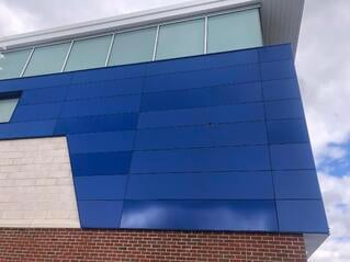Victor central school exterior phenolic panel installation close up with three blue colors  and a exposed fastener.